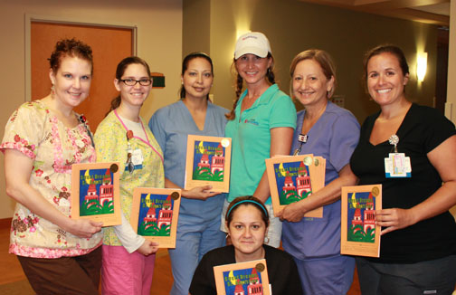 Diane Cortese donating children's books to the Flagler Hospital labor and delivery ward in celebration of Cell Phone Hospital's 40th day of business. Every month the business owners show their appreciation to the St. Augustine community by doing random acts of kindness.
