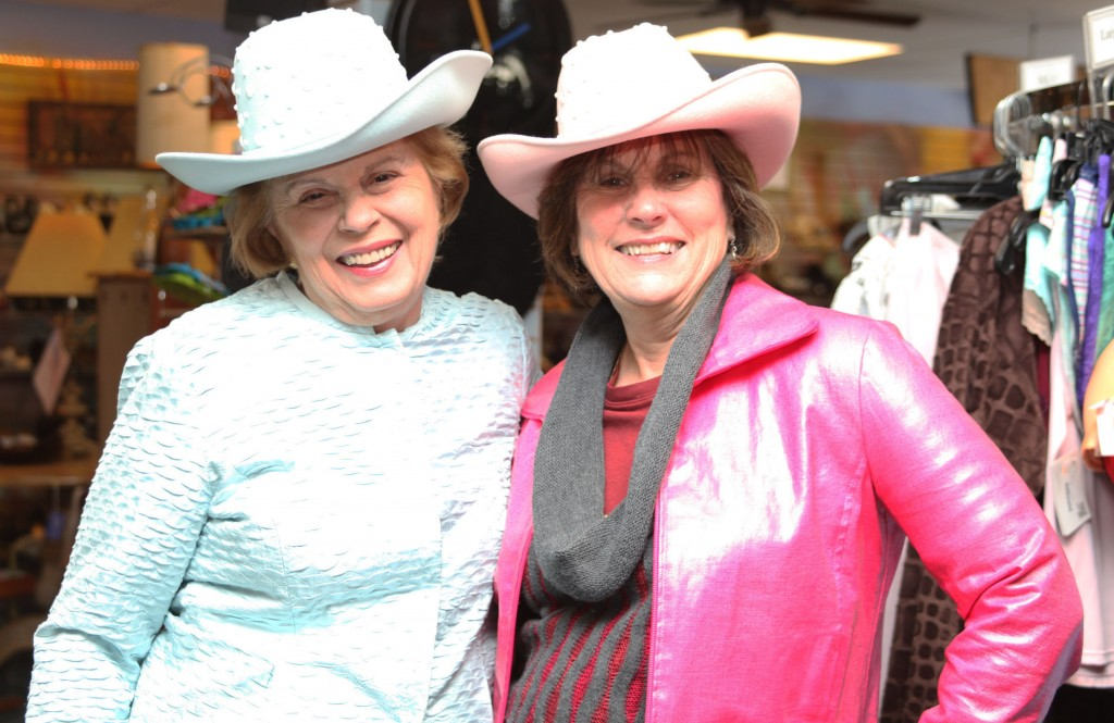 Sassy cowgirls Sandy Gaynor, left, and Sharyn Grace try on hats and jackets found at Christe Blue for the Limelight Theatre Guild's luncheon and fashion show at Marsh Creek Country Club on March 16.