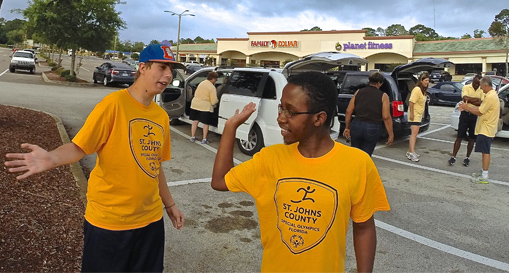 Special Olympics participants from St. Johns County high-five as they prepare to leave for the Lake Buena Vista competition May 15.
