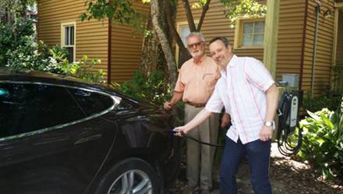 Innkeeper Joe Finnegan (left) greets guest Stefan Zander  Charging his Tesla Automobile