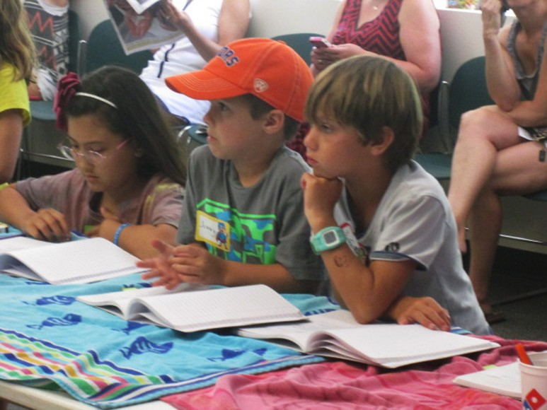 Intently listening with Nature Detective notebooks, one of many give-aways
