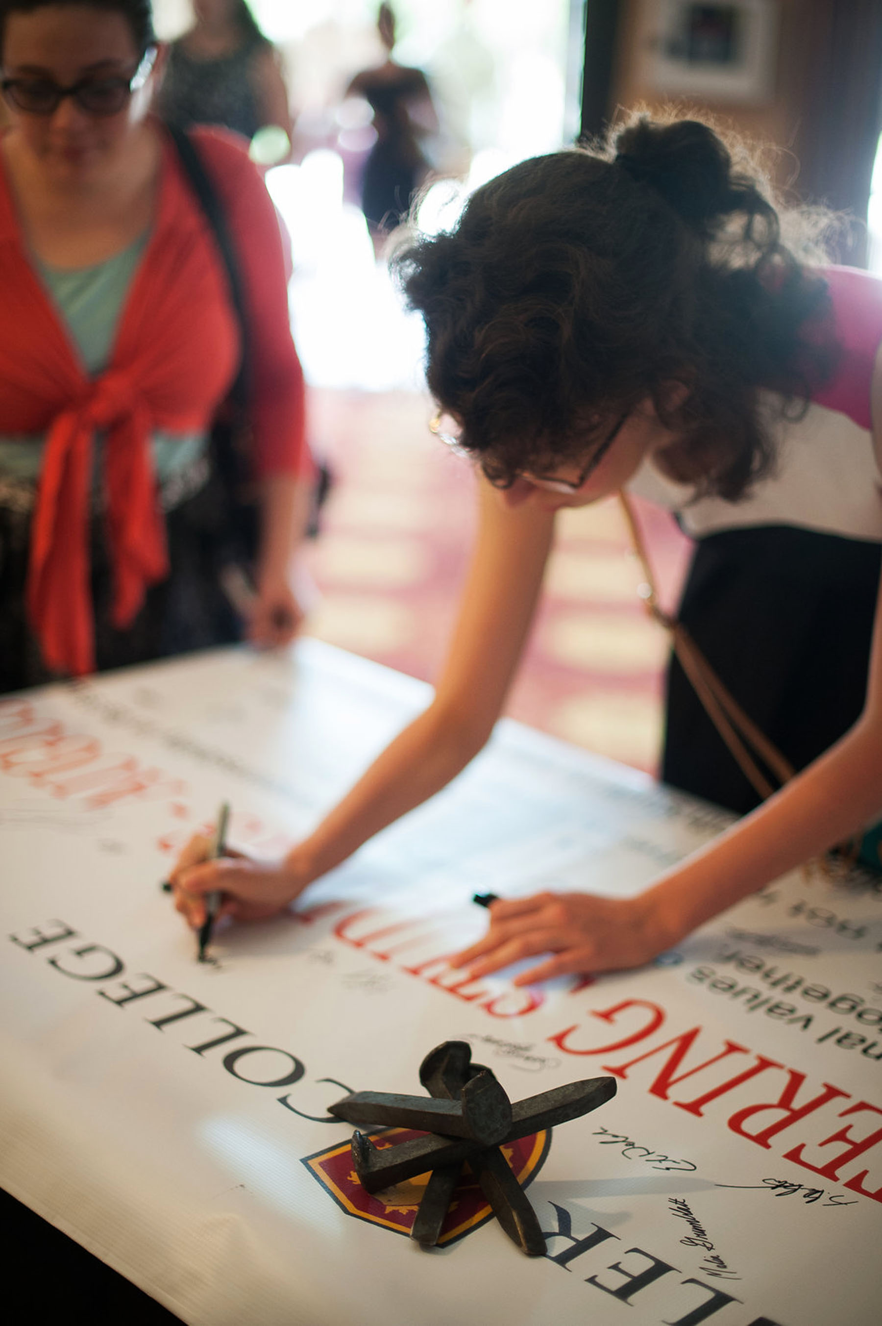 Signing the banner was part of the convocation rites at Flagler College