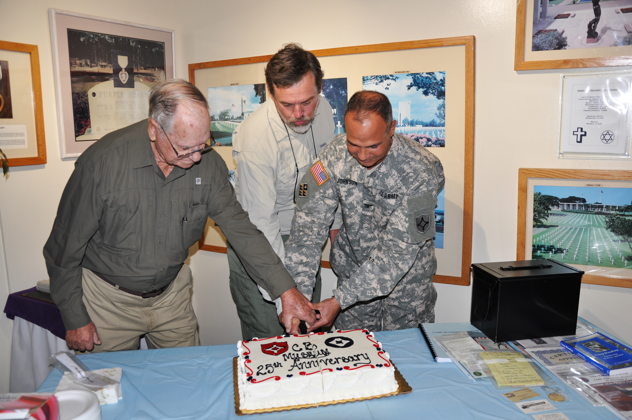 ) Rodney Hall, from left; Greg Parsons and Col. Matt Johnson cut a cake for the 25th anniversary of Camp Blanding's Museum and Memorial Gardens.