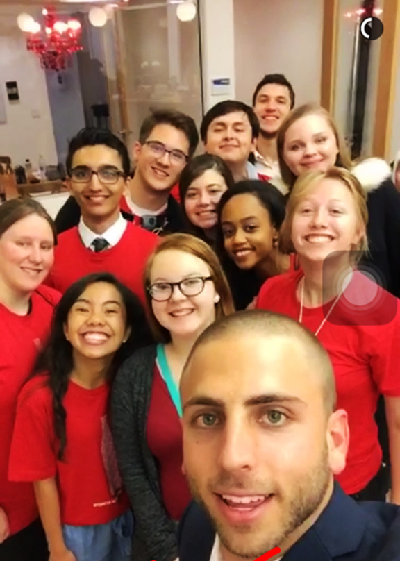 Snapchat photo of Hope Rendell, wearing glasses and teal purse, with Coca-Cola Snapchat coordinator (in foreground) and other winning students from across the United States.