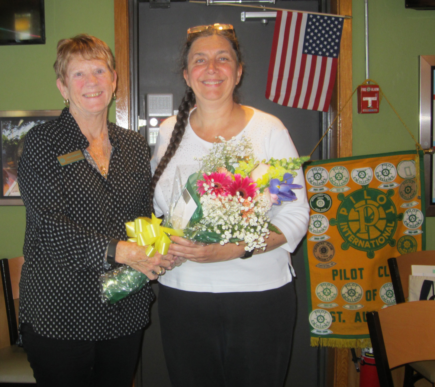 Leslie Coleman, right, receives a bouquet of flowers from Lynne Stephenson, president-elect, in honor of Coleman's election to a Florida Pilot Club district post.